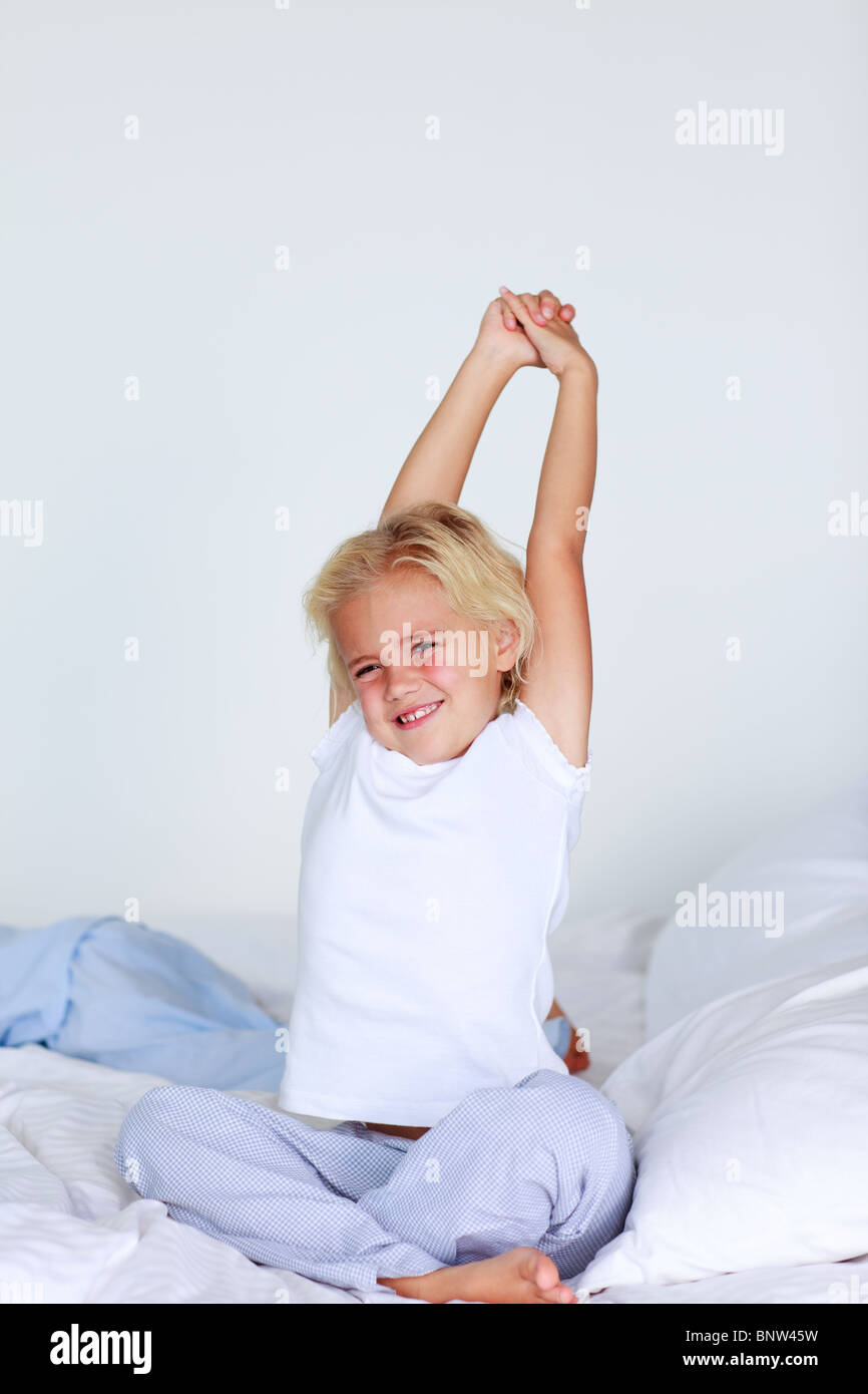 Portrait Of A Little Girl Waking Up In A Bedroom Stock