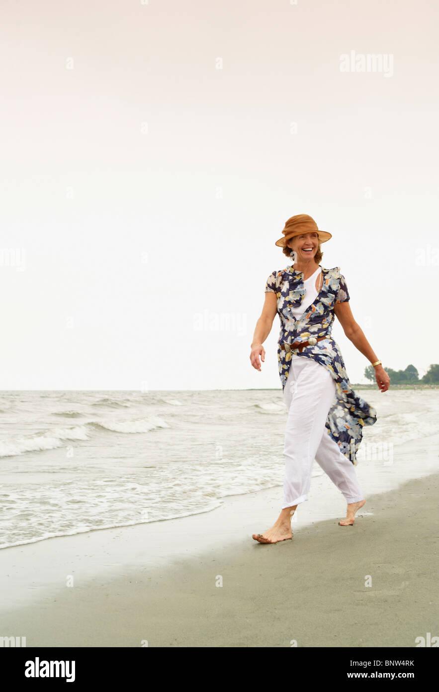 Woman walking on the beach - Stock Image