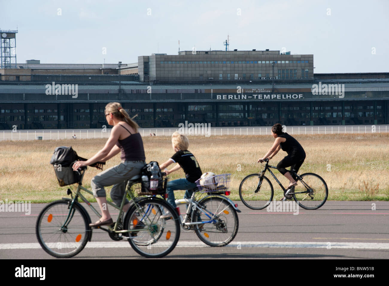 Family cycling on runway at new city public Tempelhofer Park on site of famous former Tempelhof Airport in Berlin - Stock Image