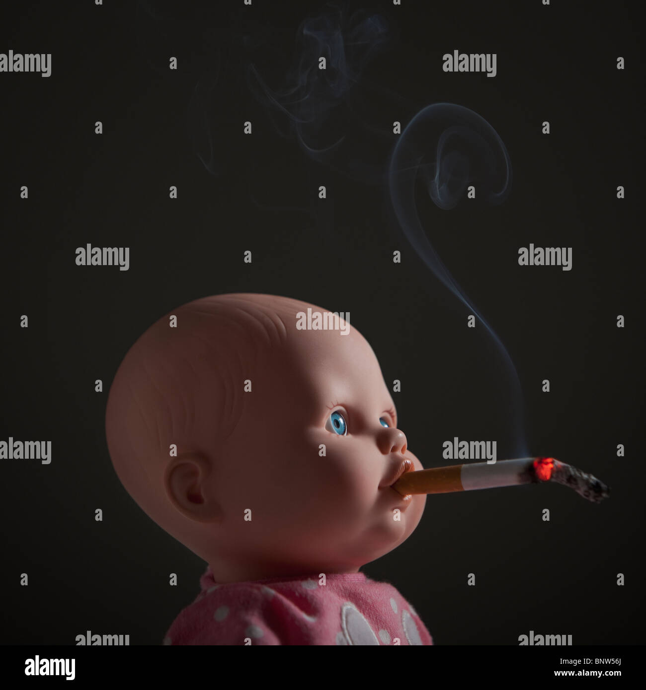Cigarette in doll's mouth - Stock Image