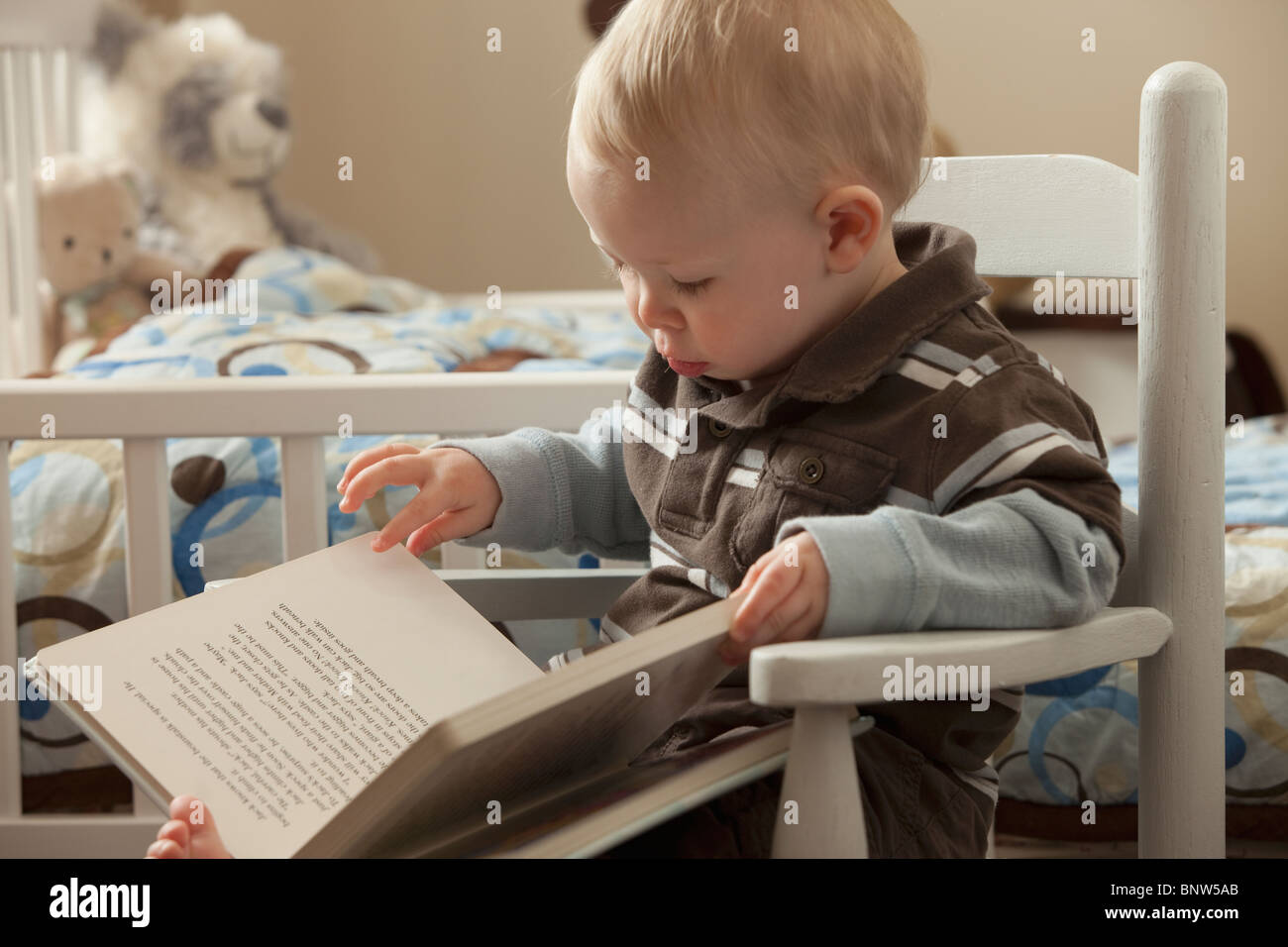 Toddler looking at a book - Stock Image