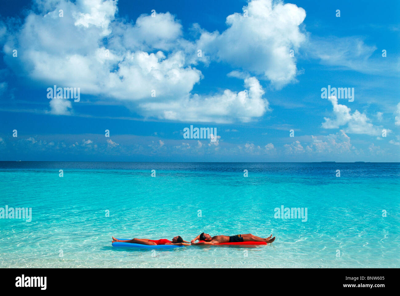 Couple floating in paradise under puffy white clouds on colorful air mattresses during idyllic island holiday - Stock Image