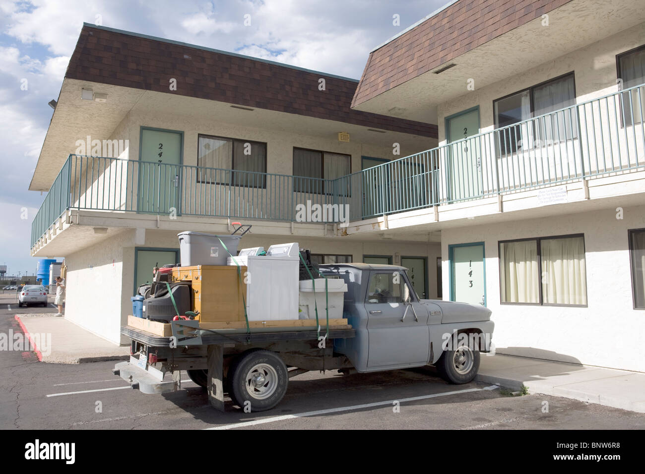 Old pickup truck loaded with household appliances and personal effects, park in front of a motel in Nebraska. - Stock Image