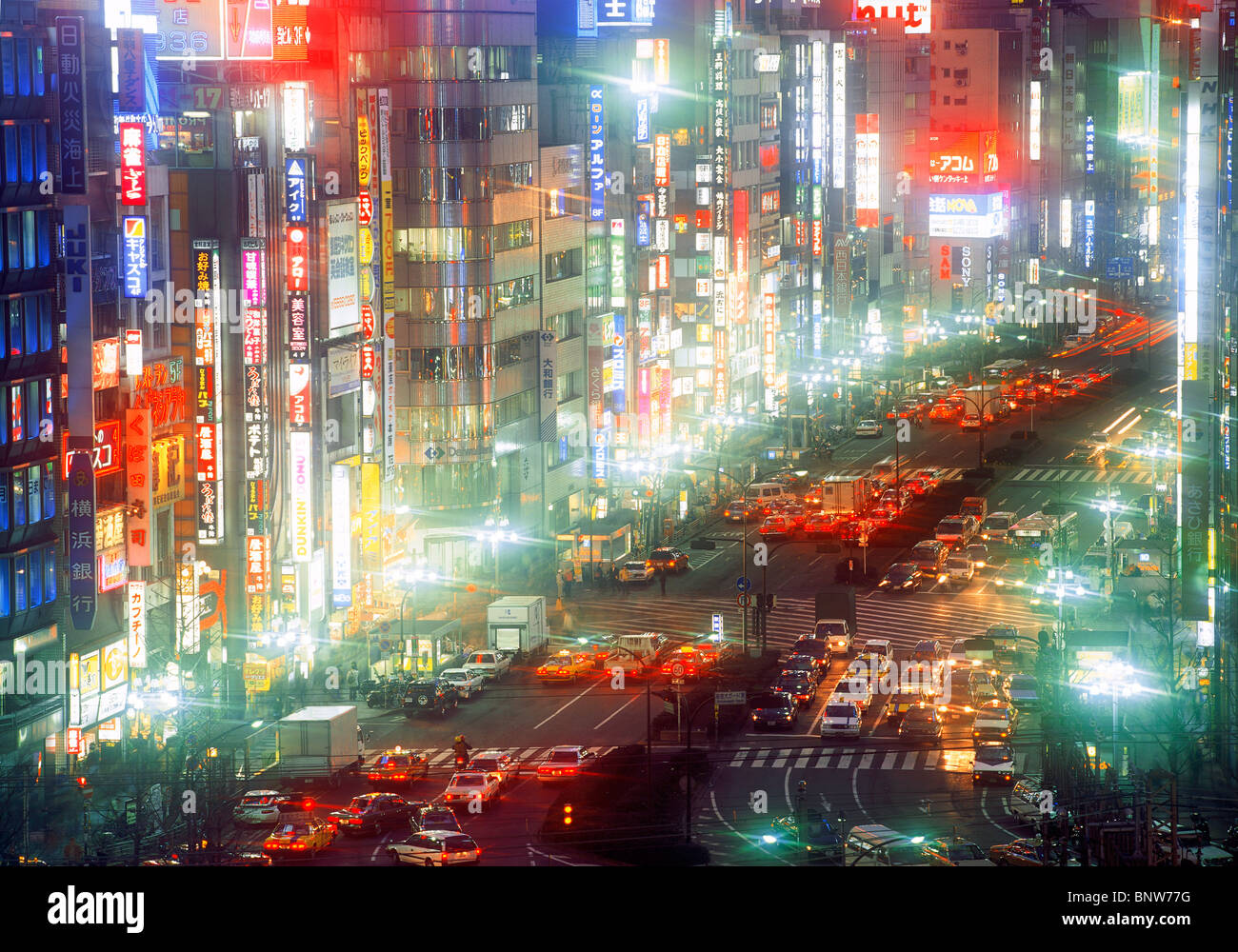 Neon lights and busy streets in Shinjuku District of Tokyo at night - Stock Image