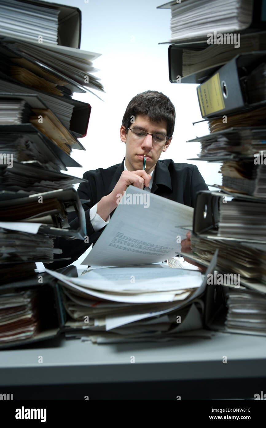 Overworked bookkeeper at his desk - Stock Image