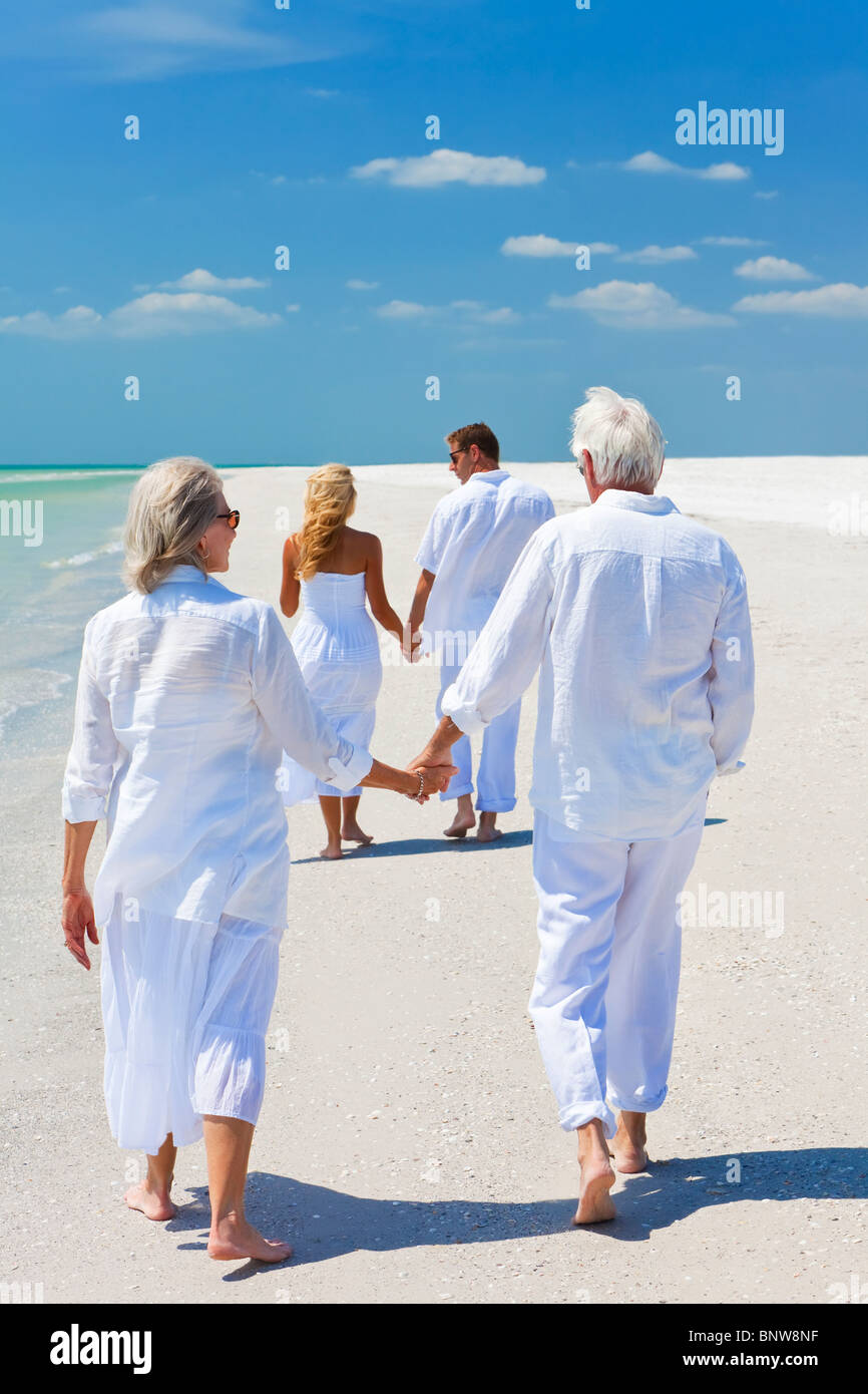 Two couples, generations of a family together holding hands and walking on a tropical beach - Stock Image
