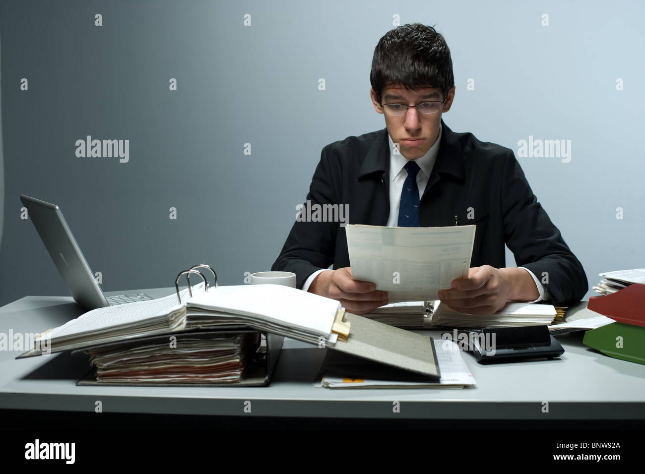 Man reading business correspondence at an office - Stock Image
