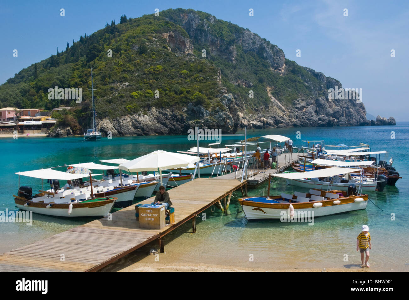 Local boatmen wait for tourists for trips around coastline at Paleokastritsa on the Greek island of Corfu Greece - Stock Image