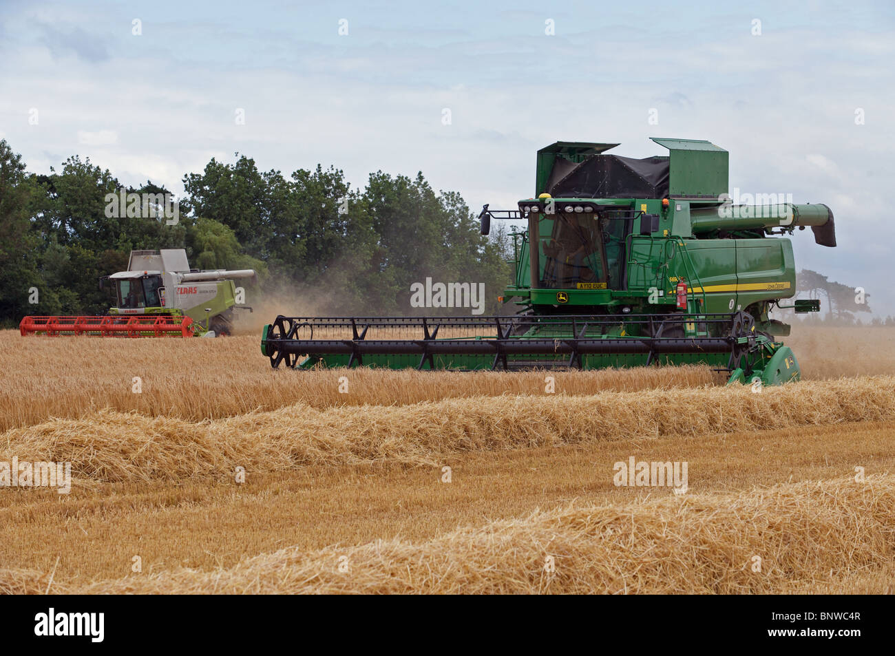 John Deere S690i and Claas Lexion 570 combine harvester working in unison cutting a field of wheat - Stock Image