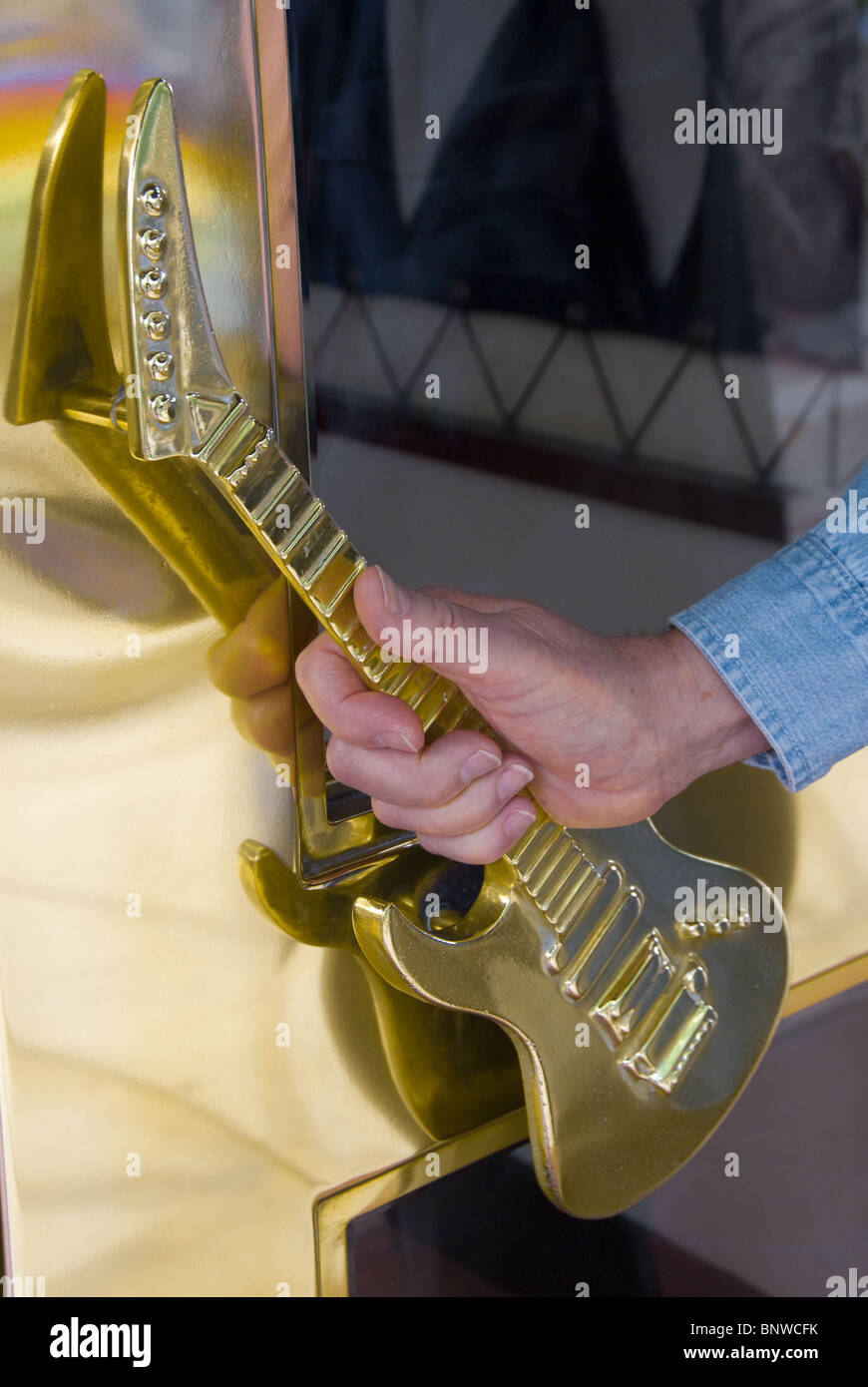 Man's hand on guitar shaped door handle at entrance of Hard Rock Cafe on the River Walk in San Antonio, Texas, - Stock Image