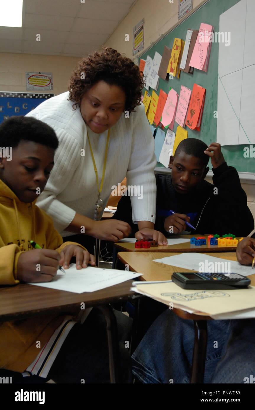 African-American teacher helps ninth grade math students work on ...