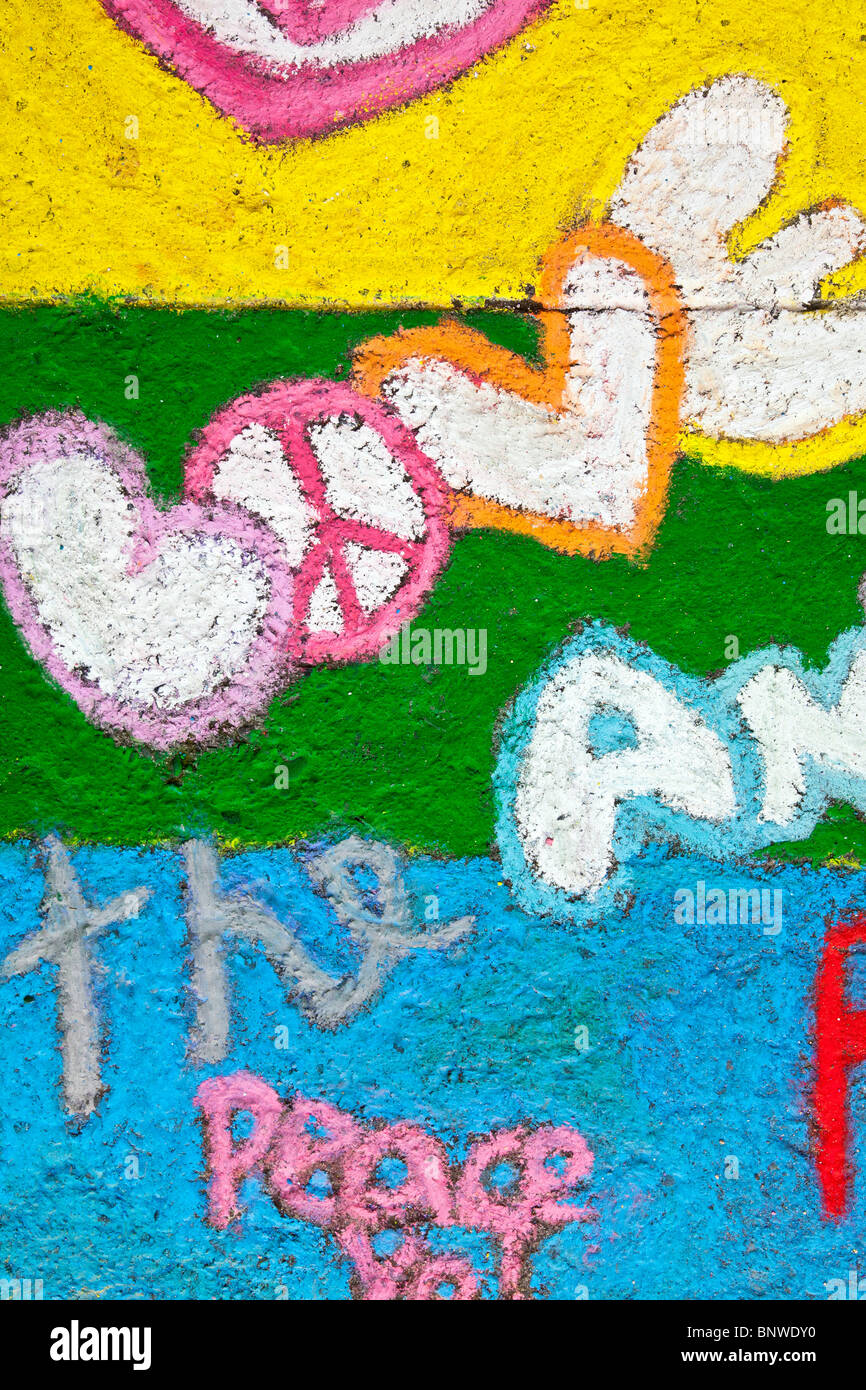 detail vivid yellow green blue sidewalk chalk drawing with gentle message of peace & love at Chalk Art Festival - Stock Image