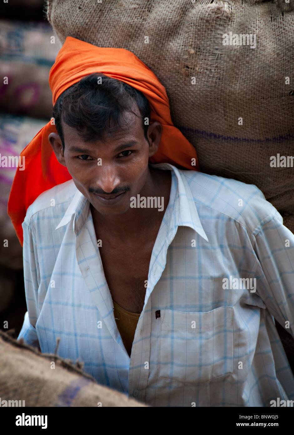 Market Worker moving Potato Sacks - Stock Image