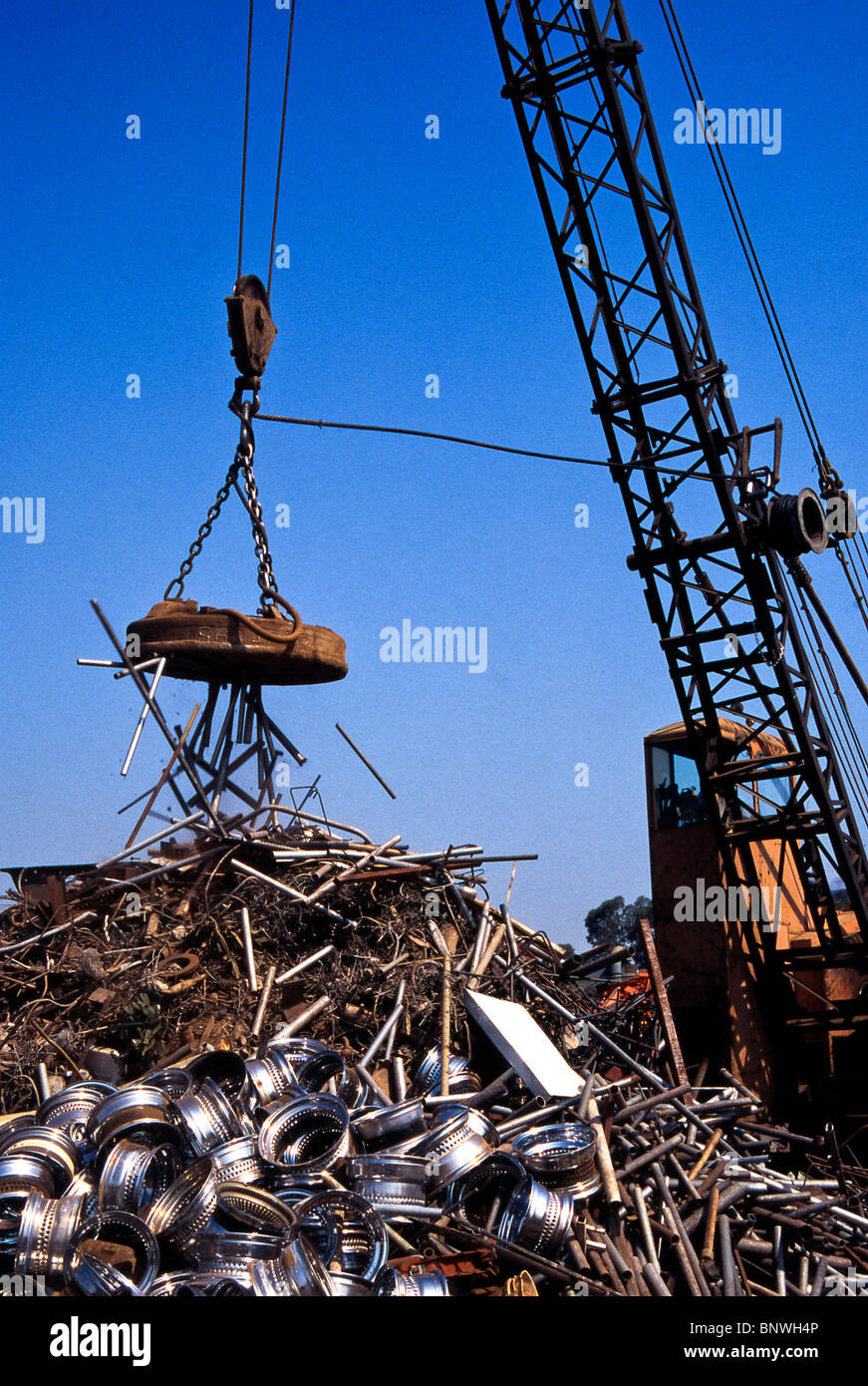 A giant crane-mounted electromagnet is used to move a pile of iron and steel items at a scrap yard in Carson, California. - Stock Image