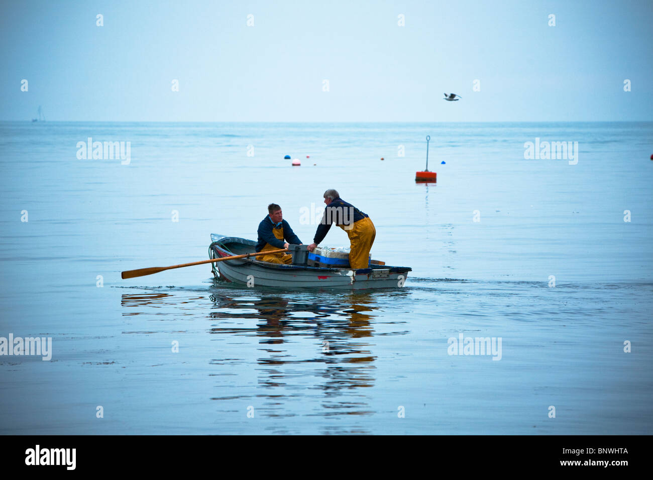 Fishermen rowing out to their fishing boat in the early morning, Swanage, Dorset, Uk - Stock Image