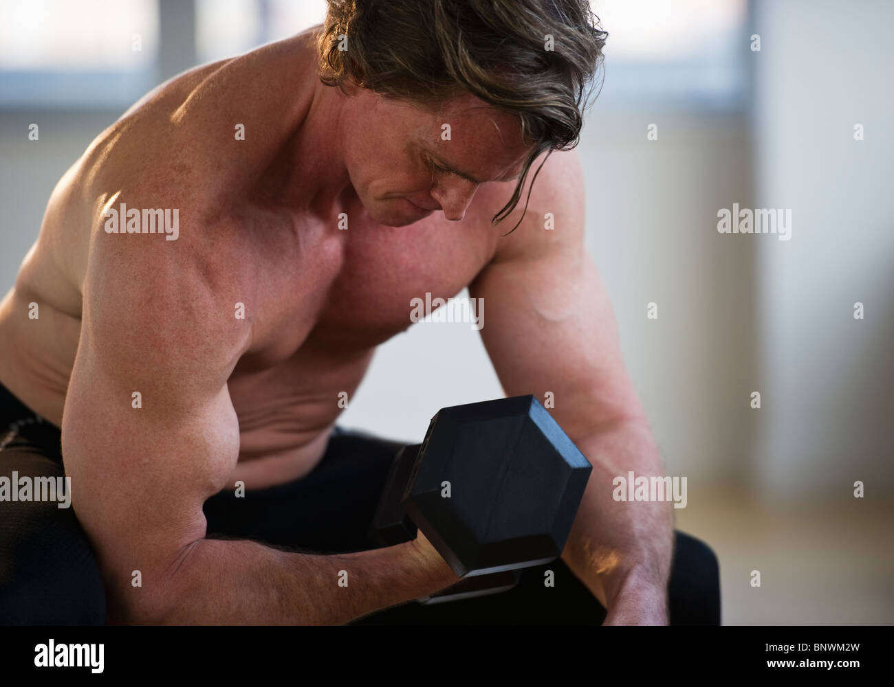 Muscular man lifting free weight - Stock Image