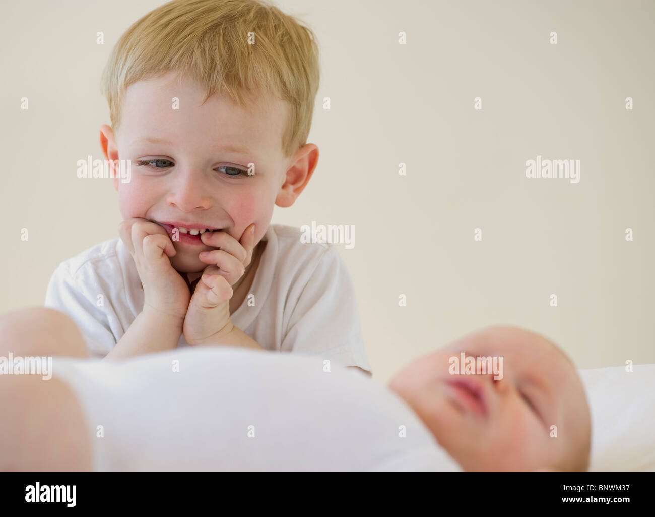 Brother watching his baby brother sleep - Stock Image