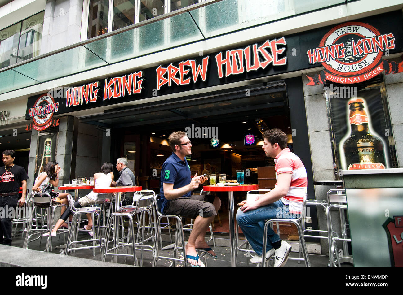 Friends enjoy a cold beer at the Hong Kong brew house located at the bustling Lan Kwai fong area in Central. - Stock Image