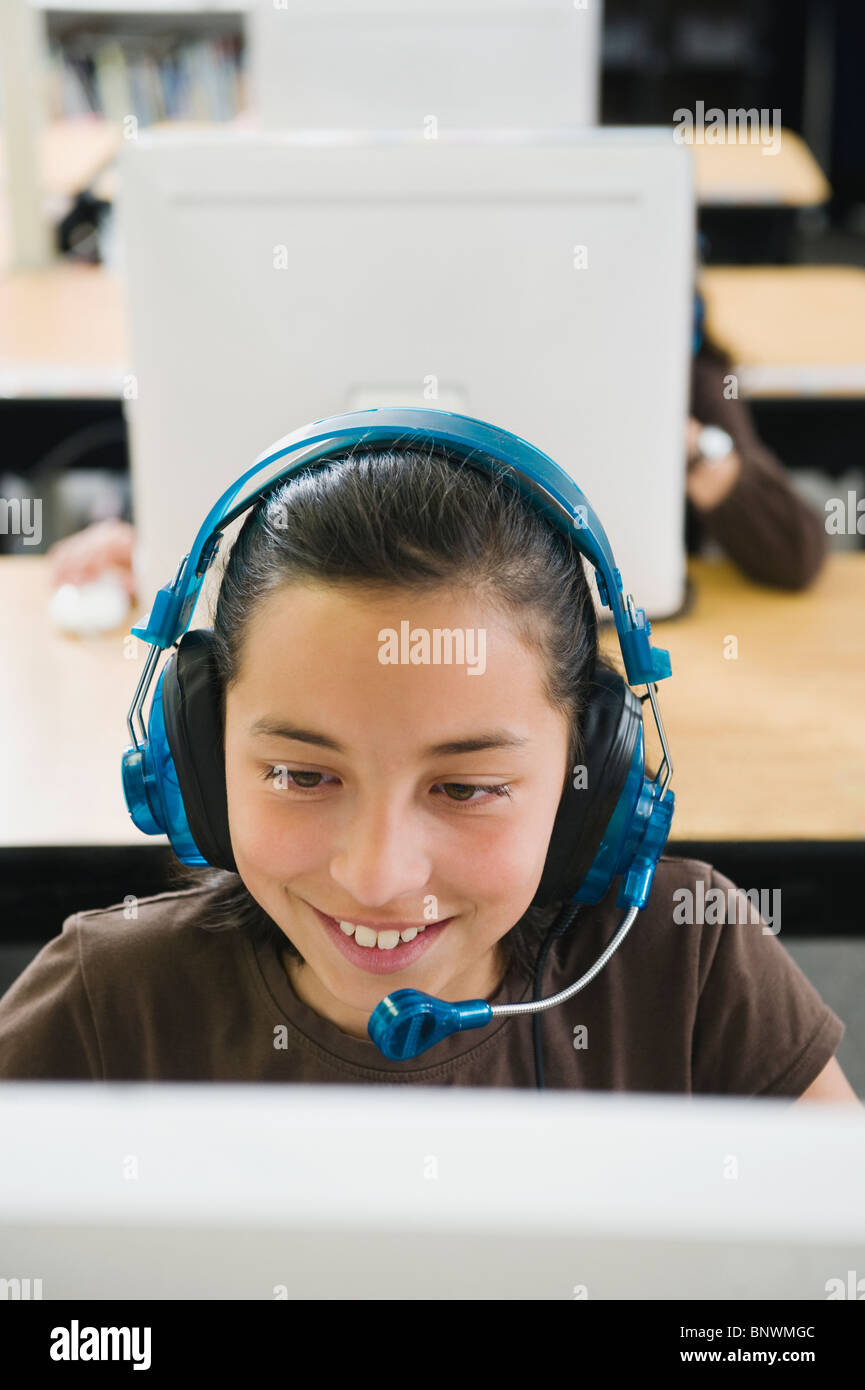 Elementary student wearing headphones in classroom Stock Photo