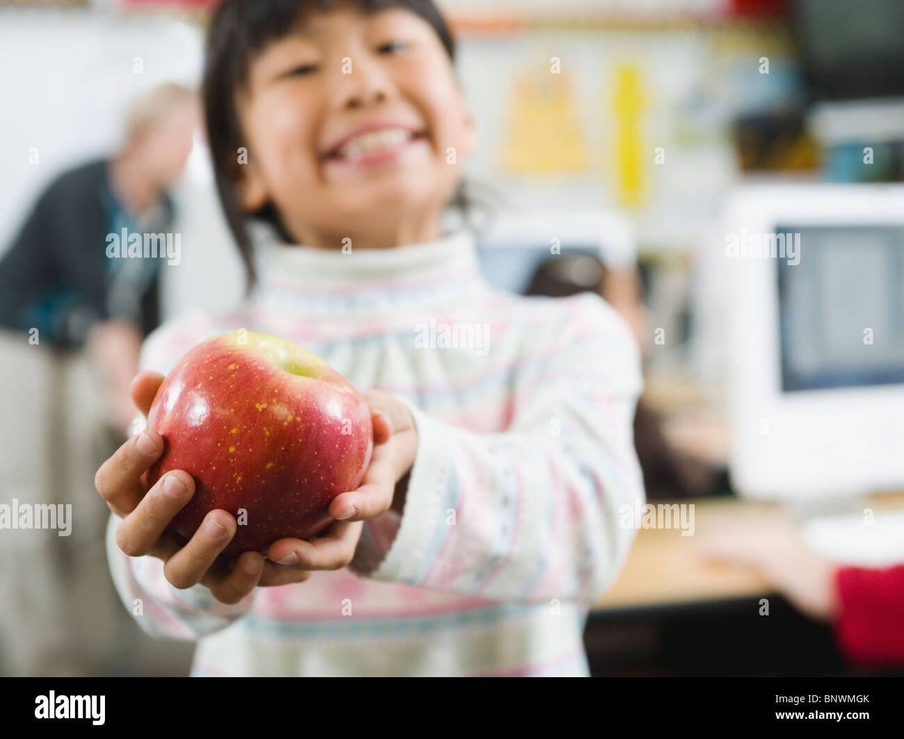 Elementary student holding an apple in her hand - Stock Image