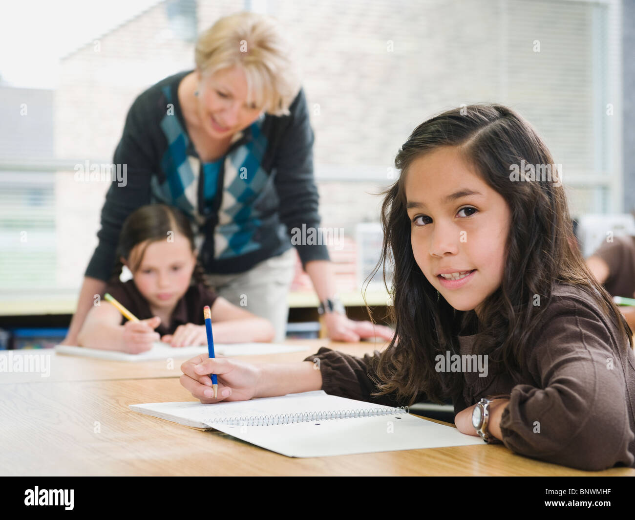 elementary students writing in their notebooks stock photo: 30683115