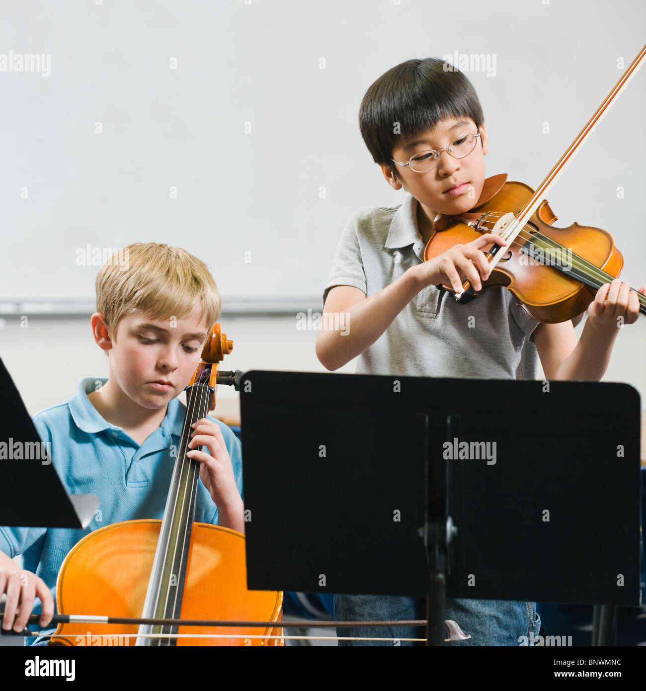 Elementary school students playing instruments in music class - Stock Image