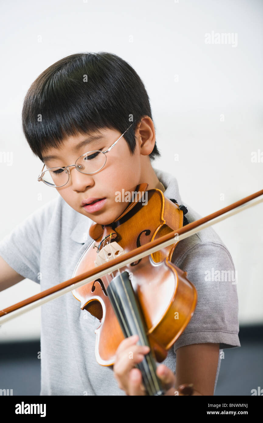 Elementary school student playing violin in music class - Stock Image
