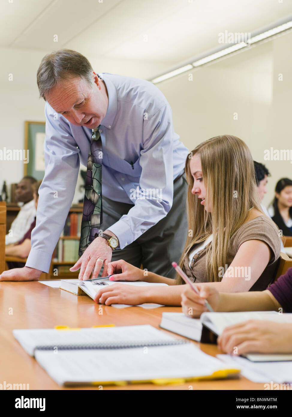Professor giving instruction to college student - Stock Image