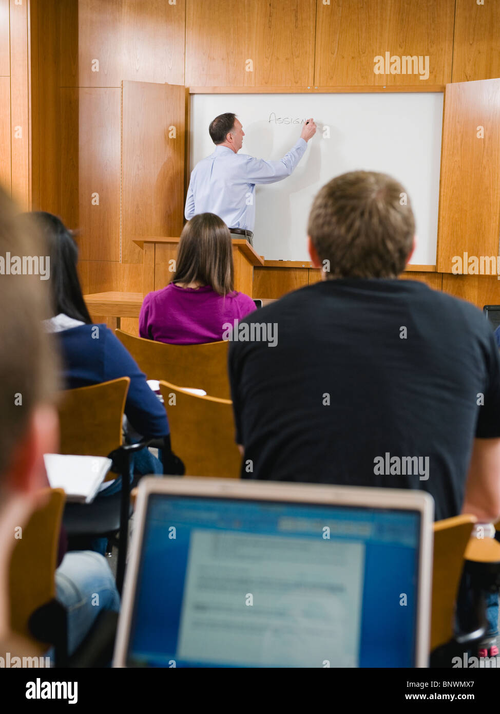 College professor giving lecture in lecture hall - Stock Image