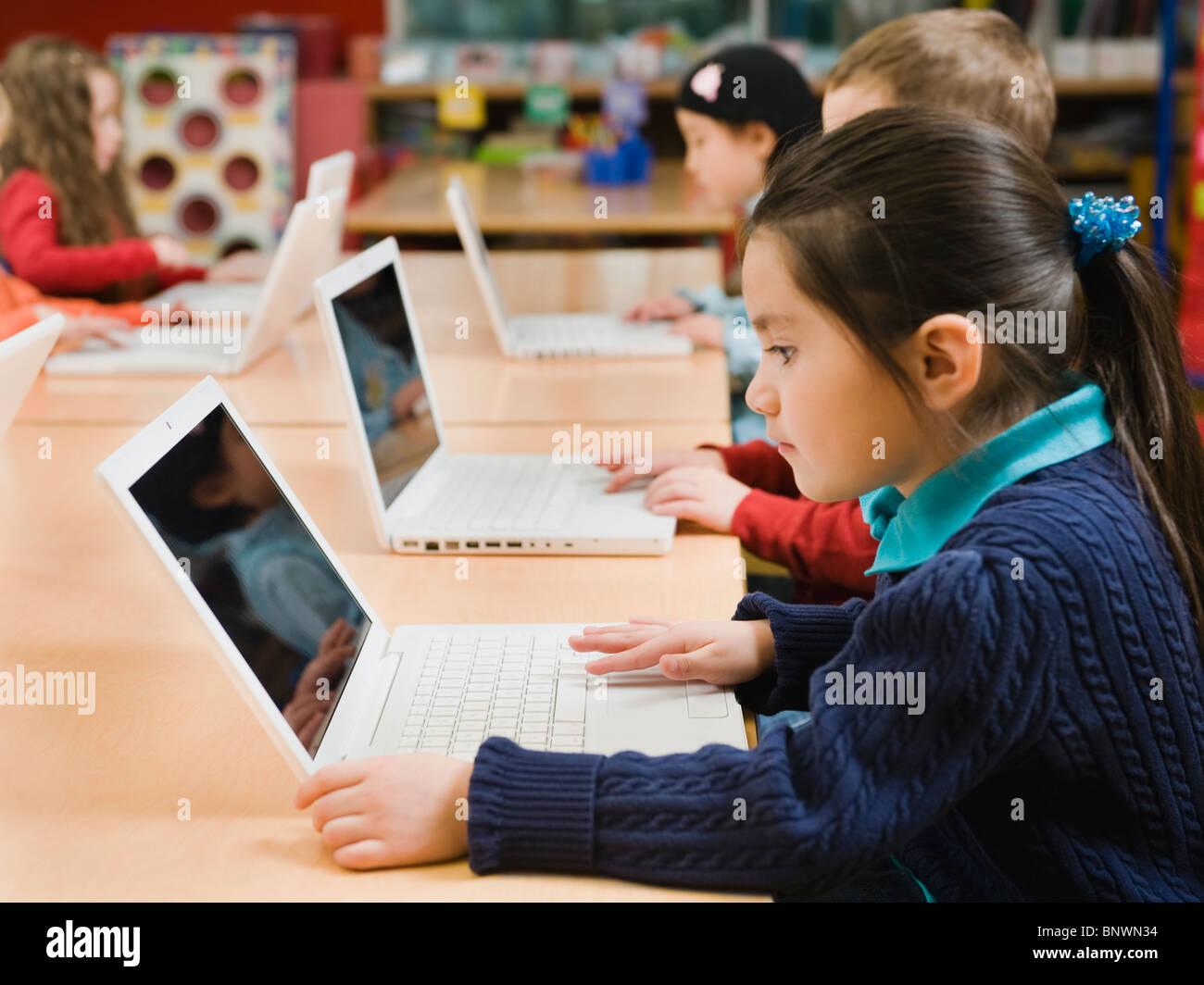 Kindergarten students working on laptops - Stock Image