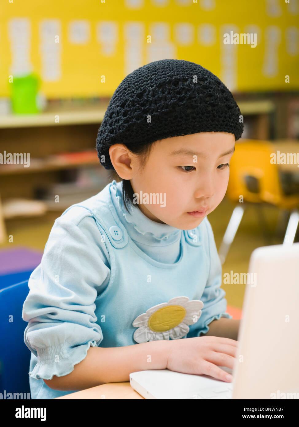 Kindergarten student working on laptop in classroom - Stock Image