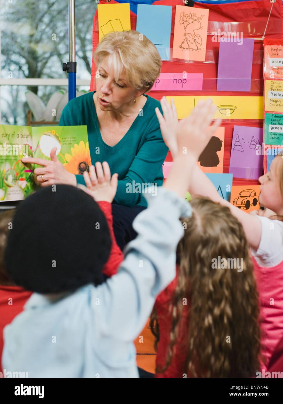 Elementary school teacher reading book to students - Stock Image