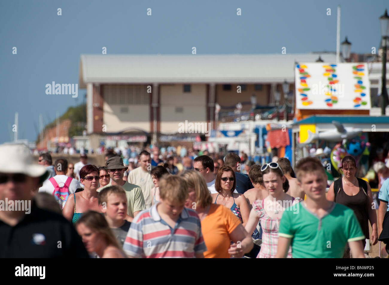 Crowds of holidaymakers enjpying a hot summers day in the English seaside resort of Hunstanton in East Anglia. - Stock Image