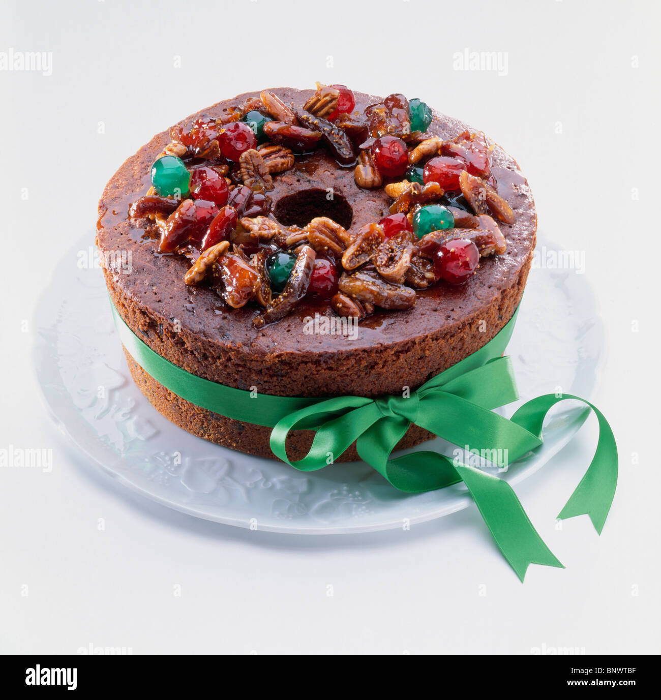 Green ribbon tied to spiced minced meat cake topped with glazed nuts and cherries - Stock Image