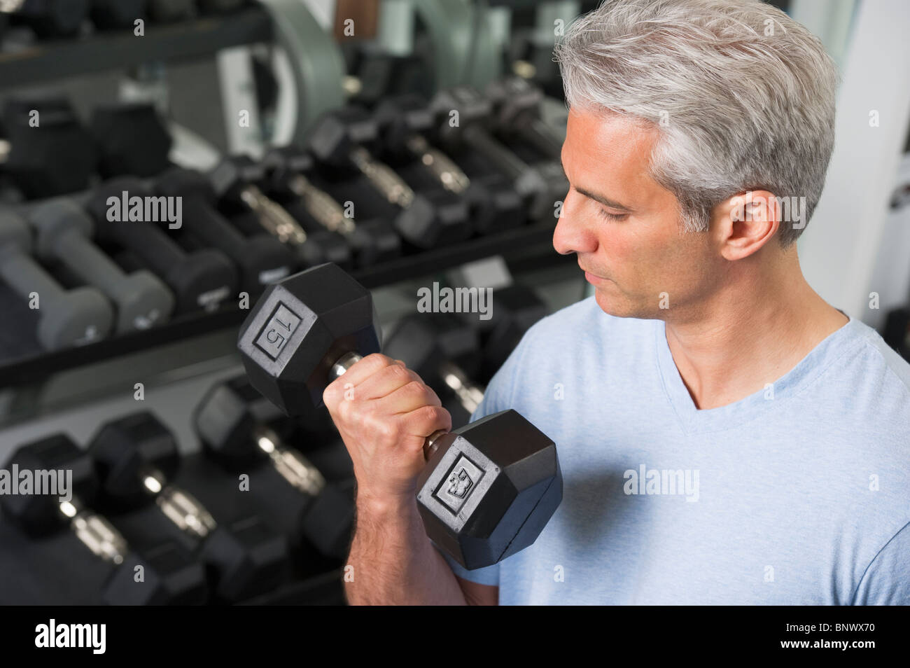 Man lifting free weights at the gym - Stock Image