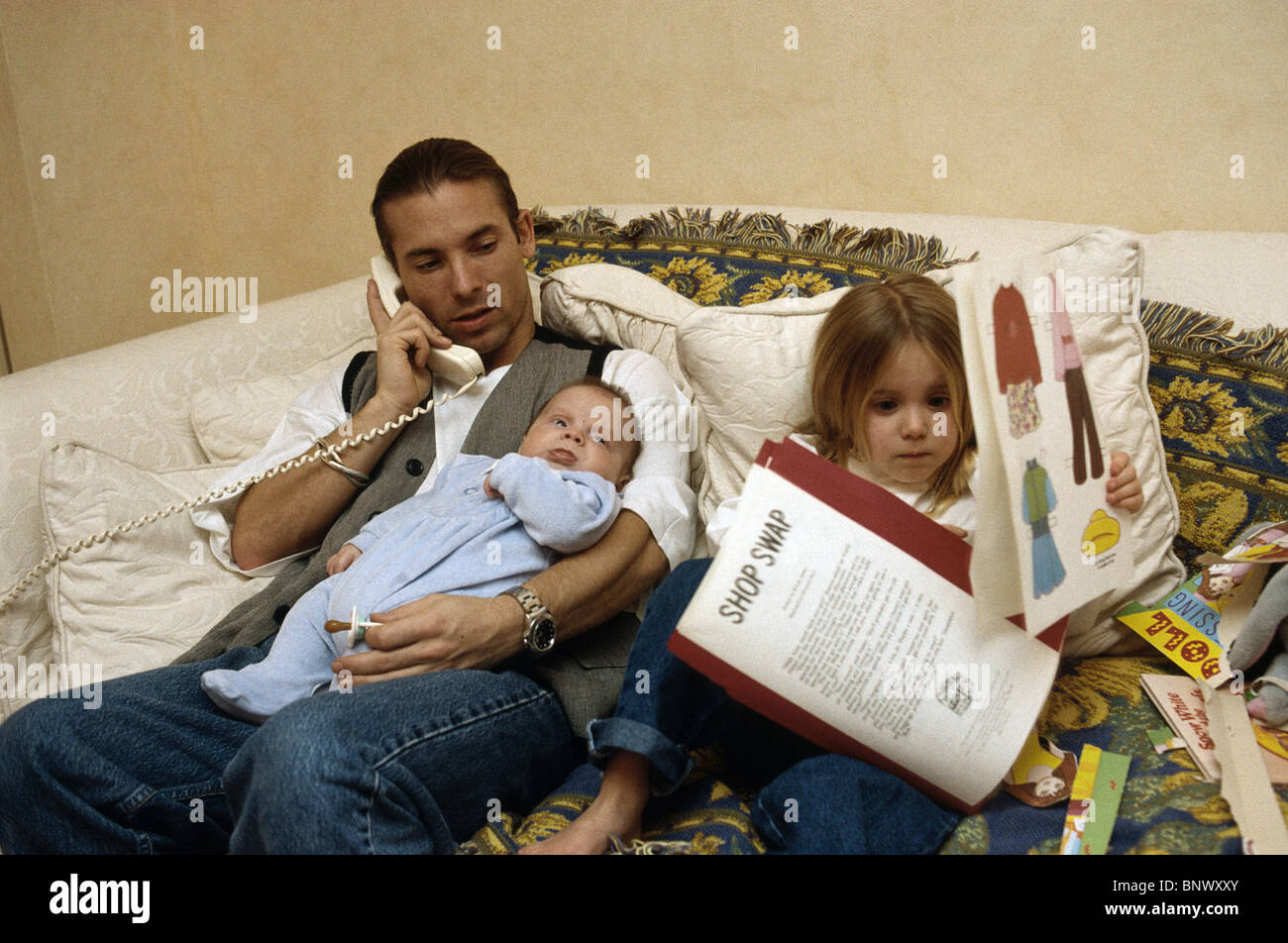 father on the phone while holding the baby and watching his daughter playing - Stock Image