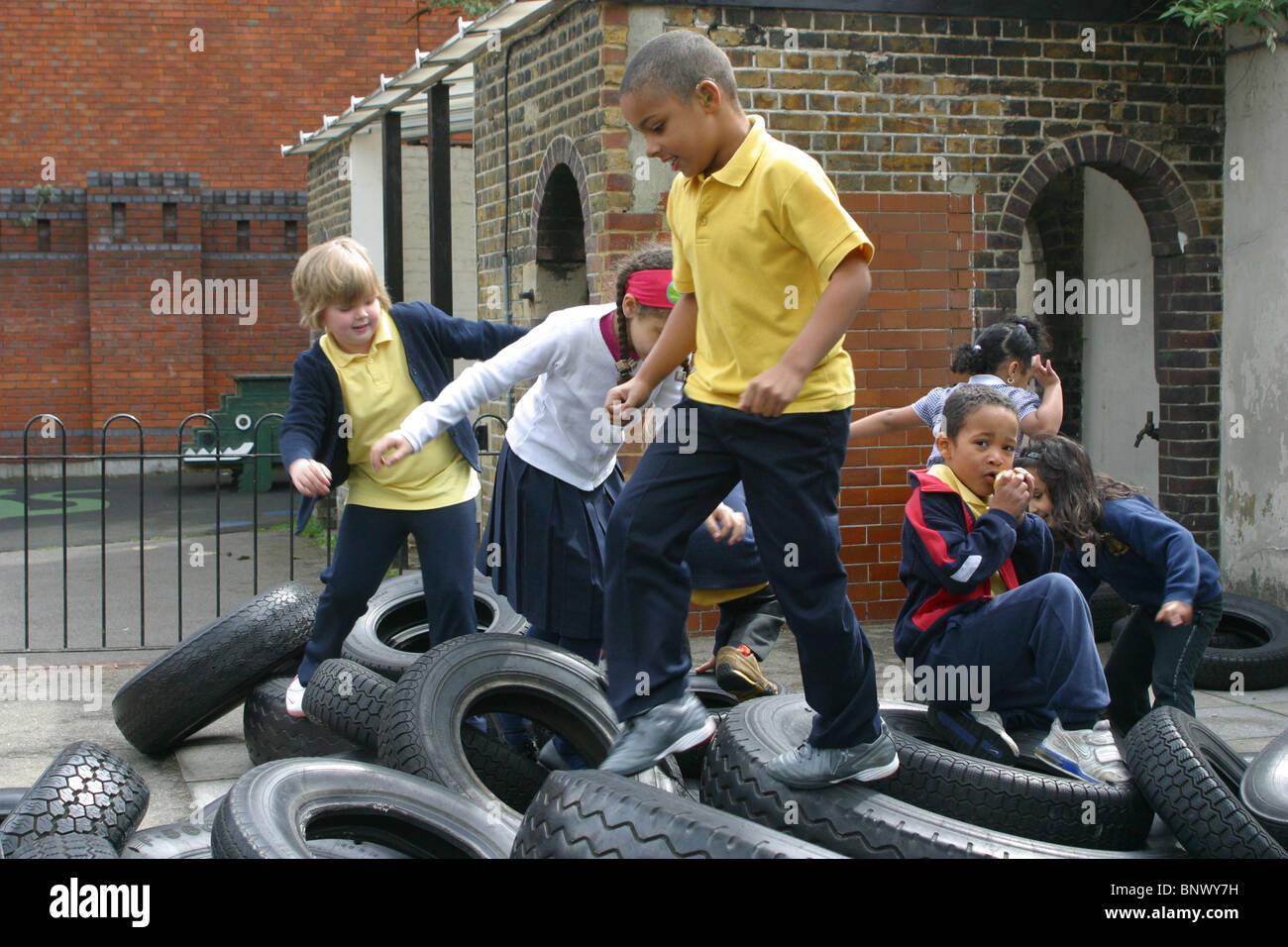 primary school children playing on old tires in the school playground - Stock Image