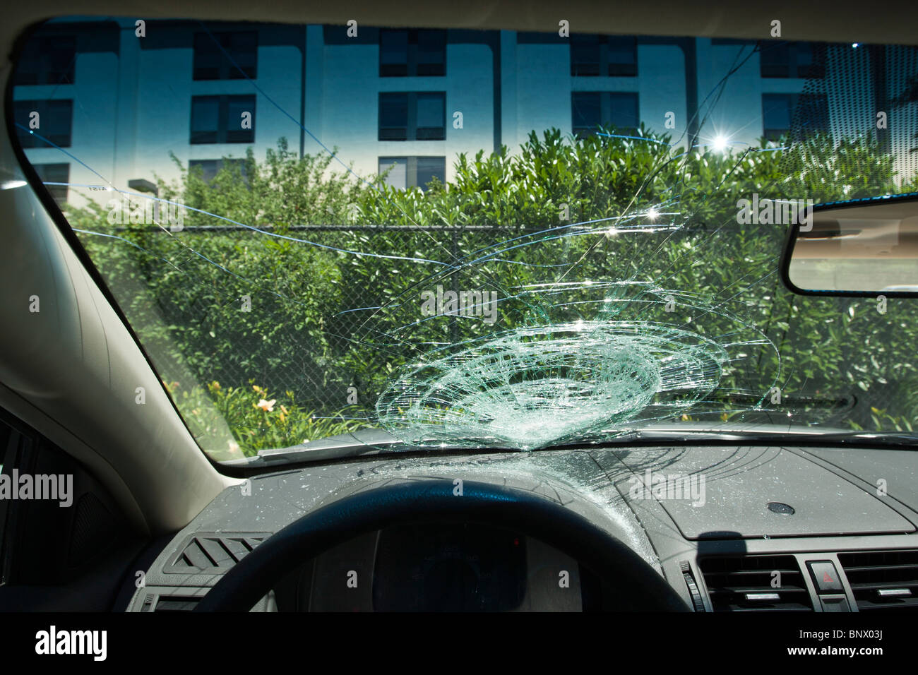 smashed front windscreen of a parked car - Stock Image