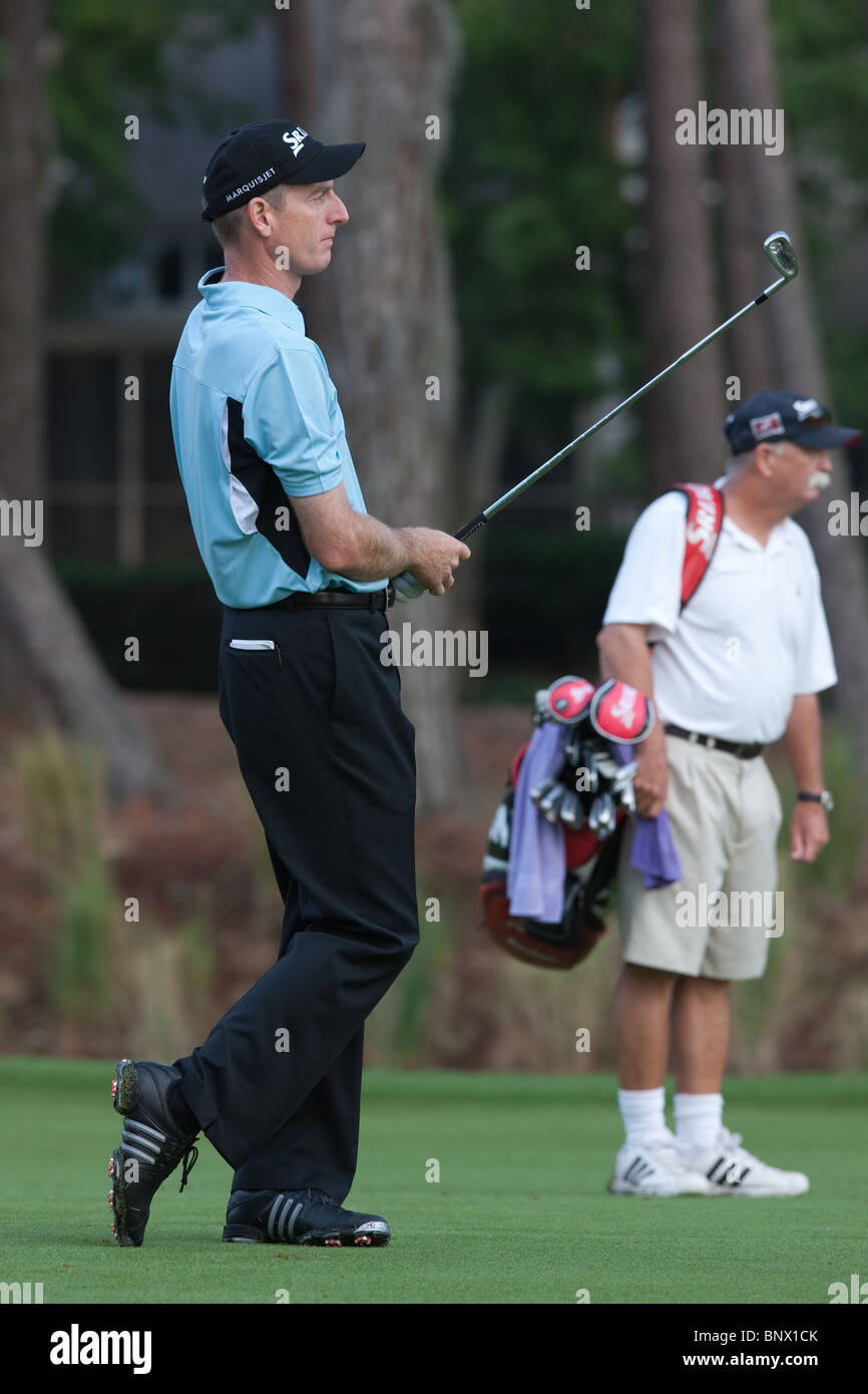Jim Furyk hits his approach shot on the par 4 10th hole while caddie 'Fluff' Cowan looks on during practice - Stock Image
