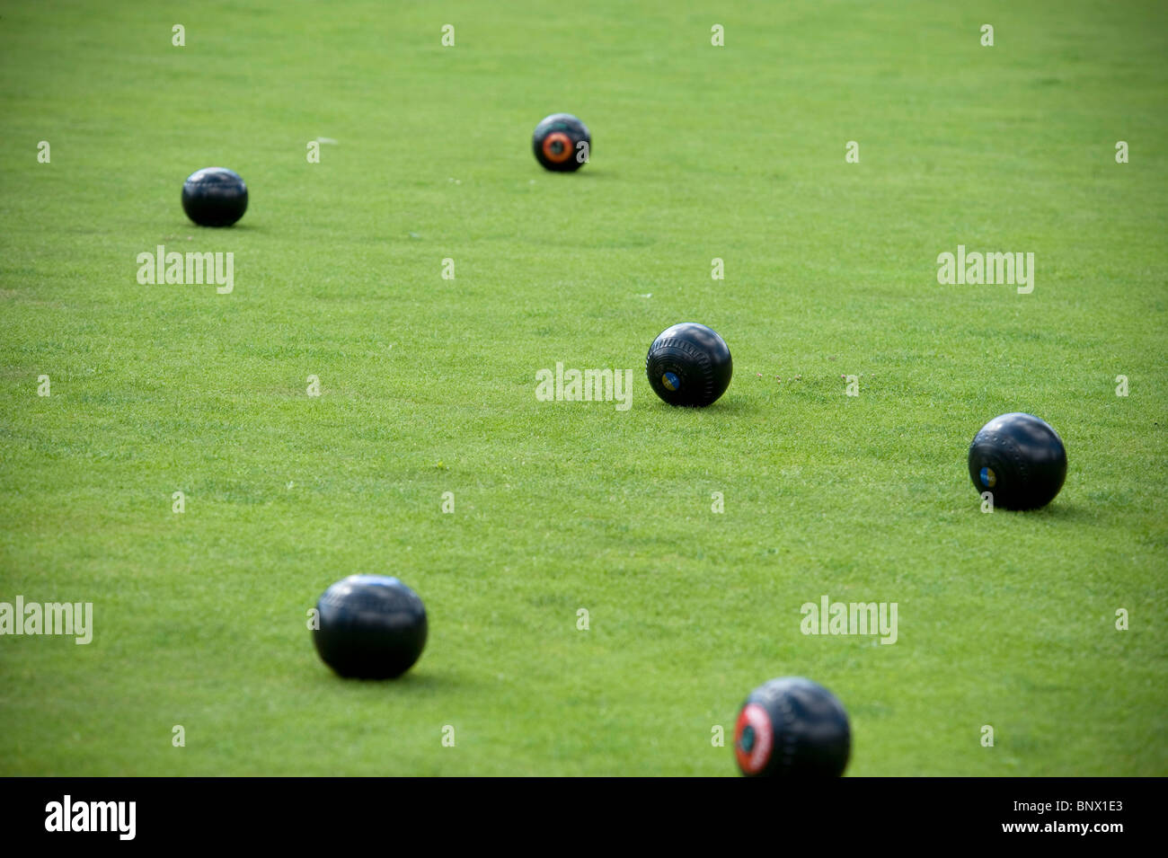 six bowls spread over the green in a game of lawn bowls - Stock Image