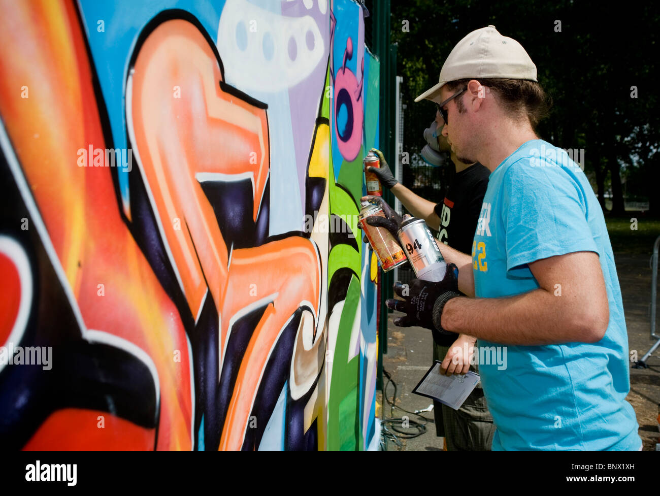 Graffiti Artists At The Brent Respect Festival Making A Mural With Spray Cans Wearing Protective Masks