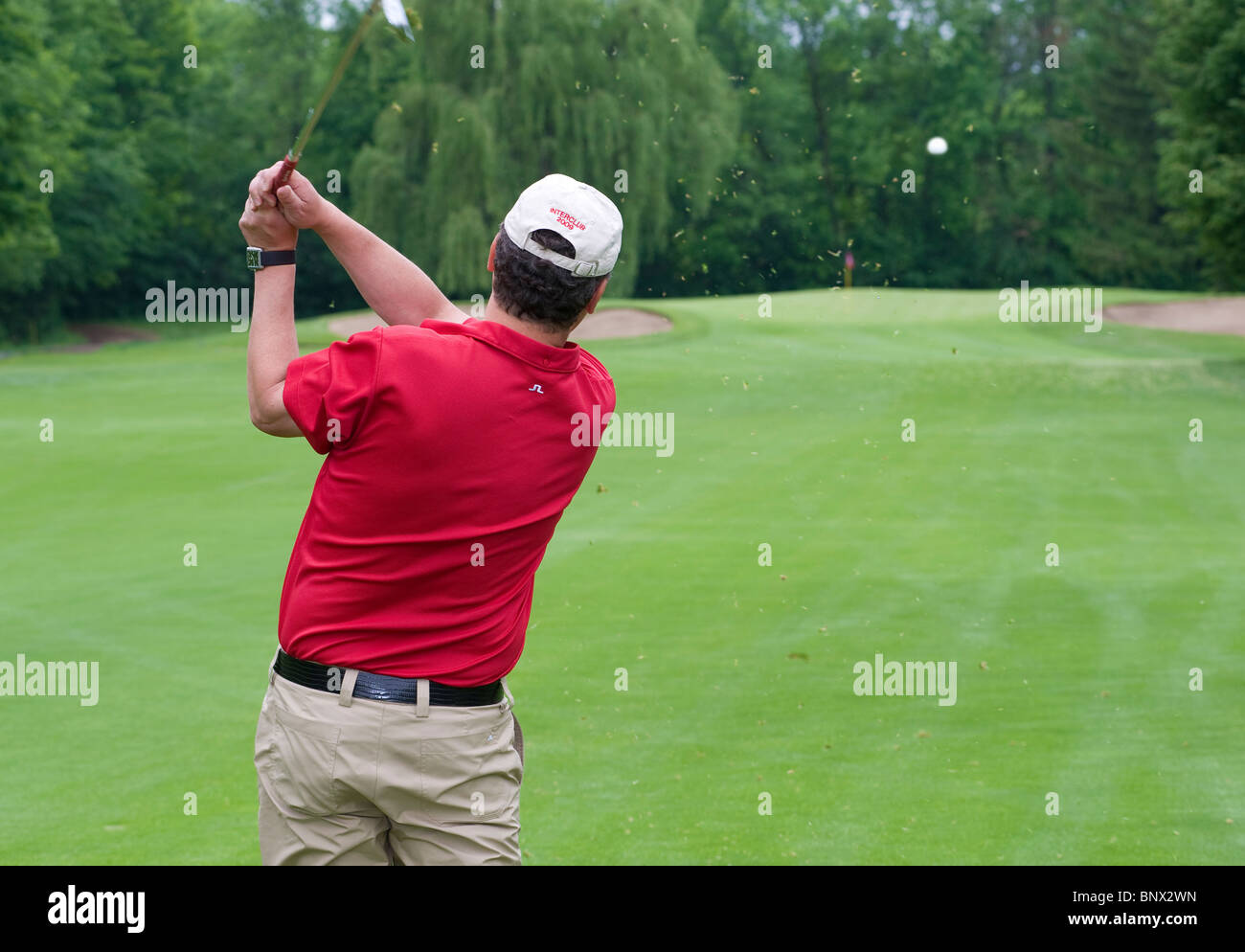 A golfer watches his ball flying towards the green. - Stock Image