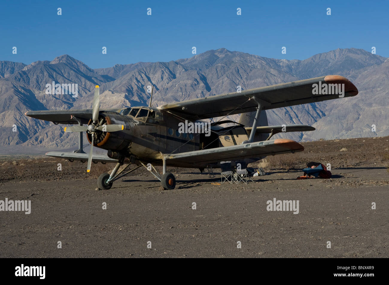 Antonov AN-2 biplane parked at Chicken Strip Saline Valley Death Valley National Park California near hot springs - Stock Image
