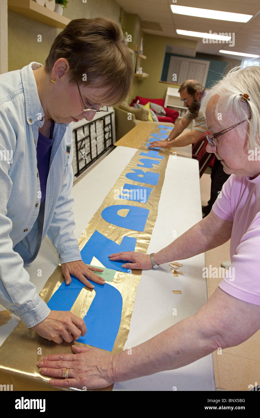 Zion Lutheran Church's Liturgical Arts Committee makes banners for Pentecost to hang in the church's sanctuary. - Stock Image