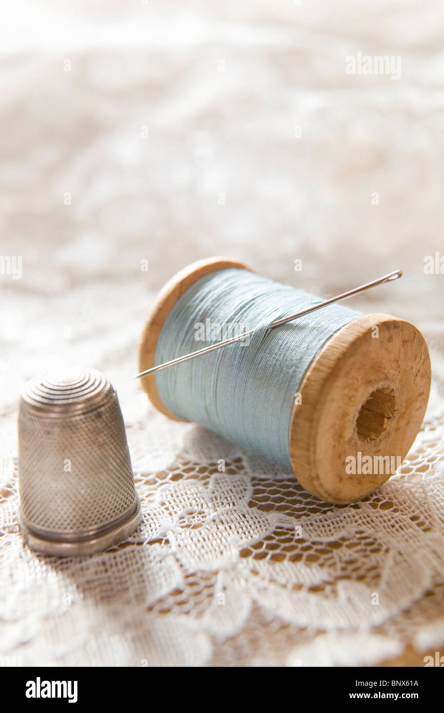 Vintage Cotton Reel With Needle And Silver Thimble On White Lace - Stock Image