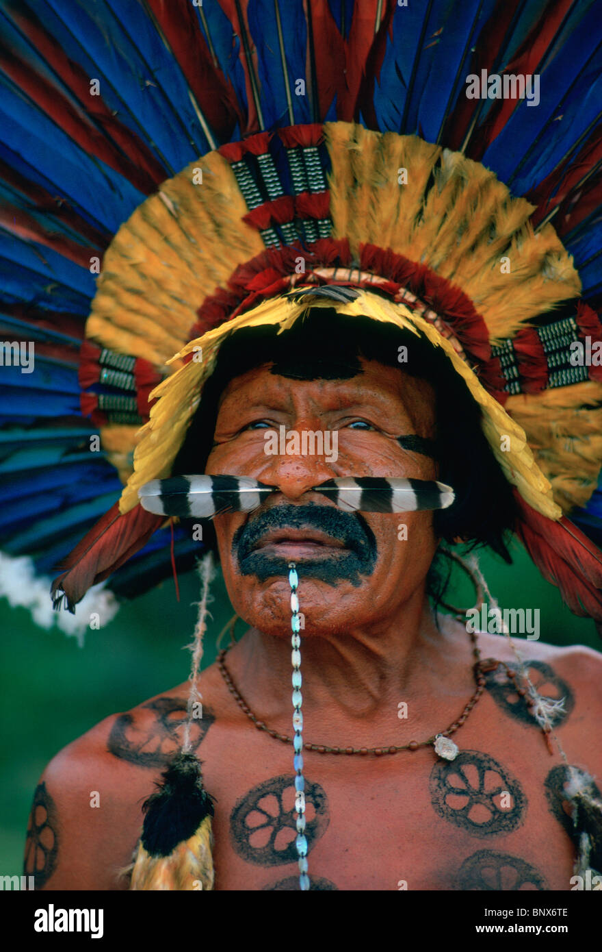Portrait of a Bororo chieftain, wearing feather headdress and other adornments, Mato Grosso, Brazil - Stock Image