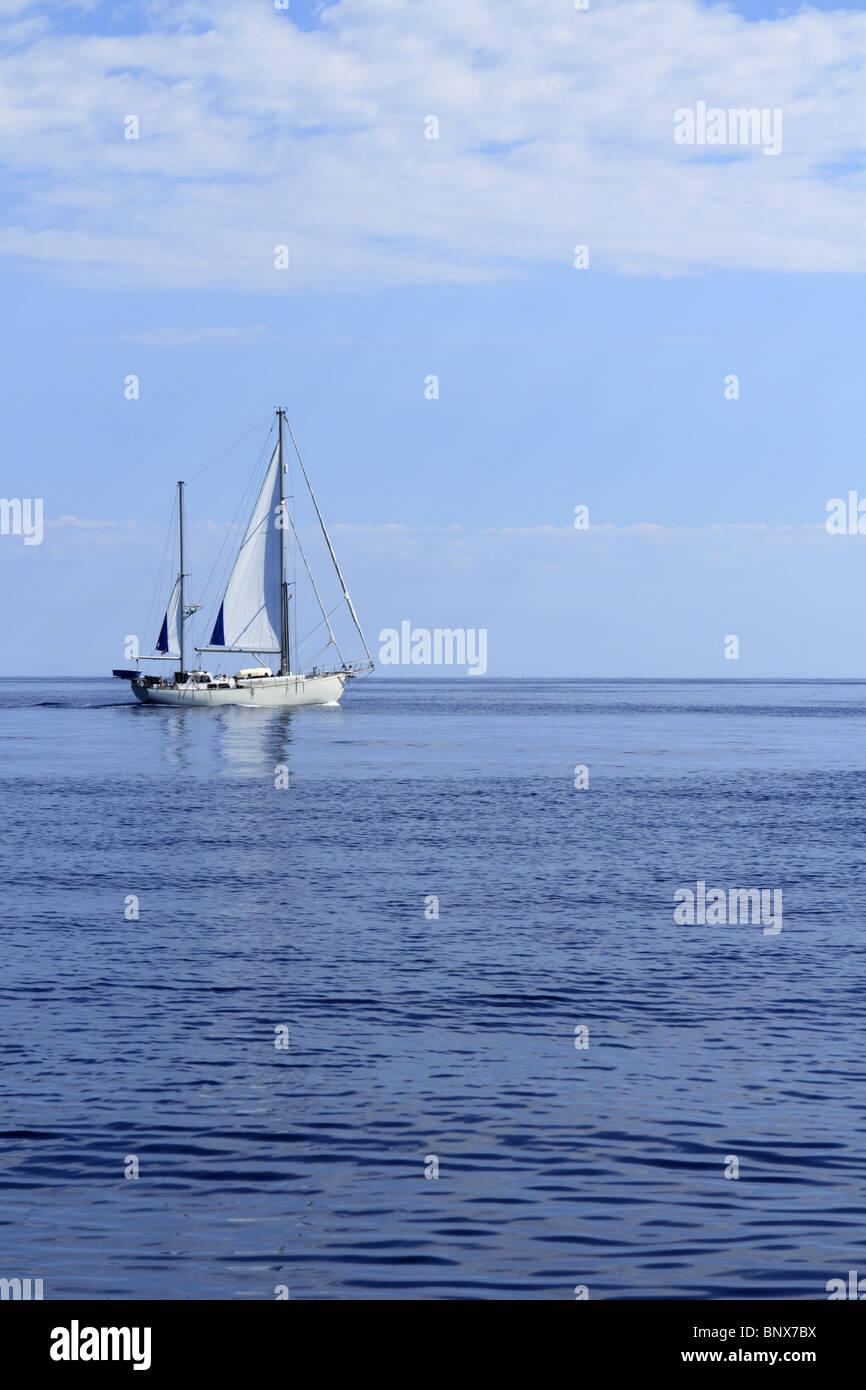 Sailboat sailing on blue sea horizon ocean perfect seascape - Stock Image