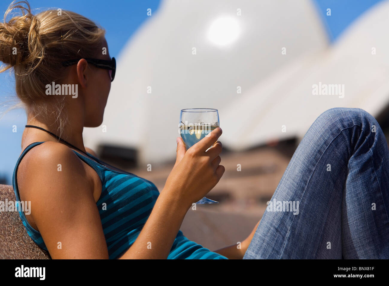 A woman enjoys a glass of wine at the Opera Bar with the Opera House in the background.  Sydney, New South Wales, - Stock Image