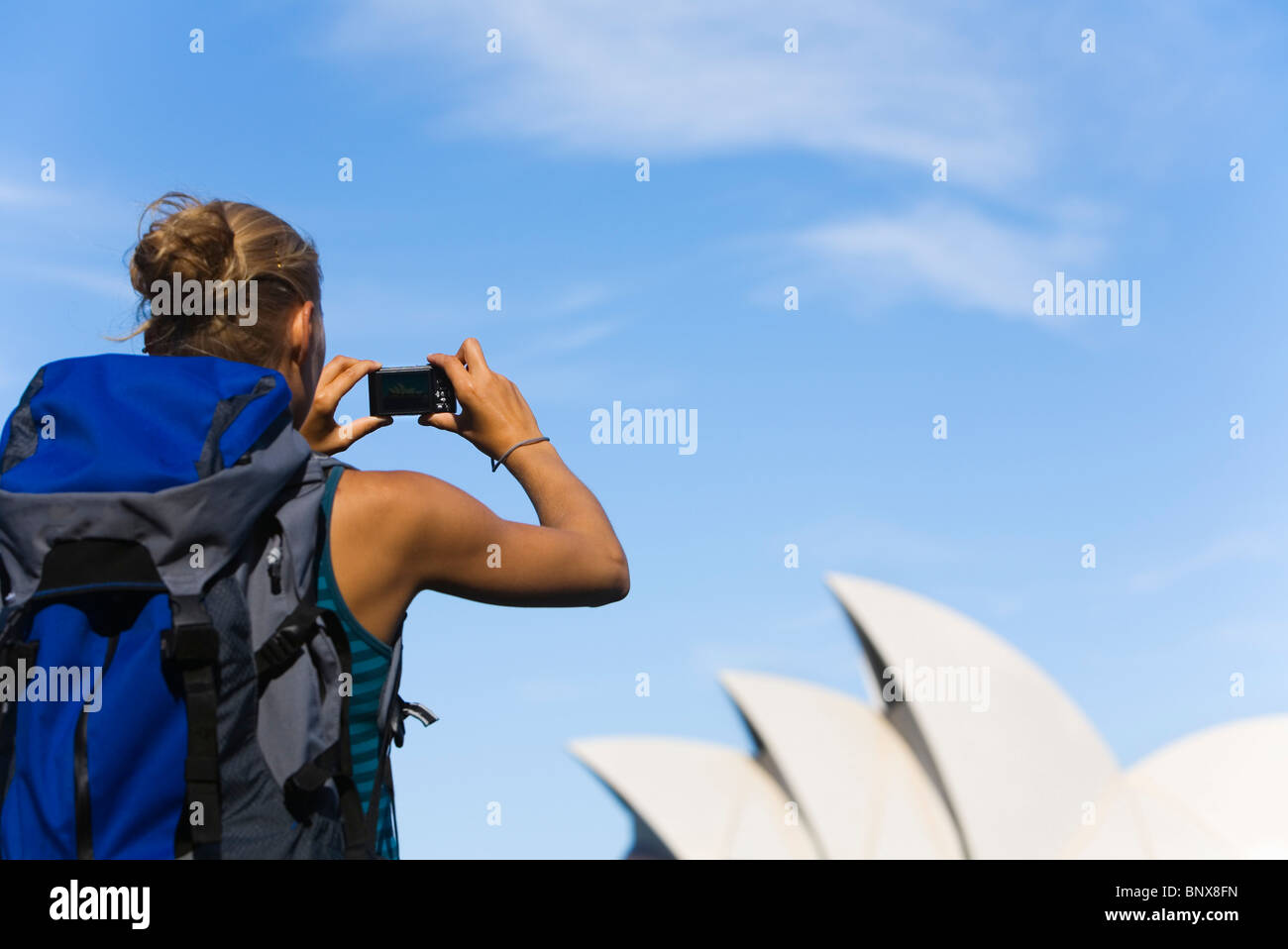 A backpacker photographs the Opera House in Sydney, New South Wales, AUSTRALIA. - Stock Image