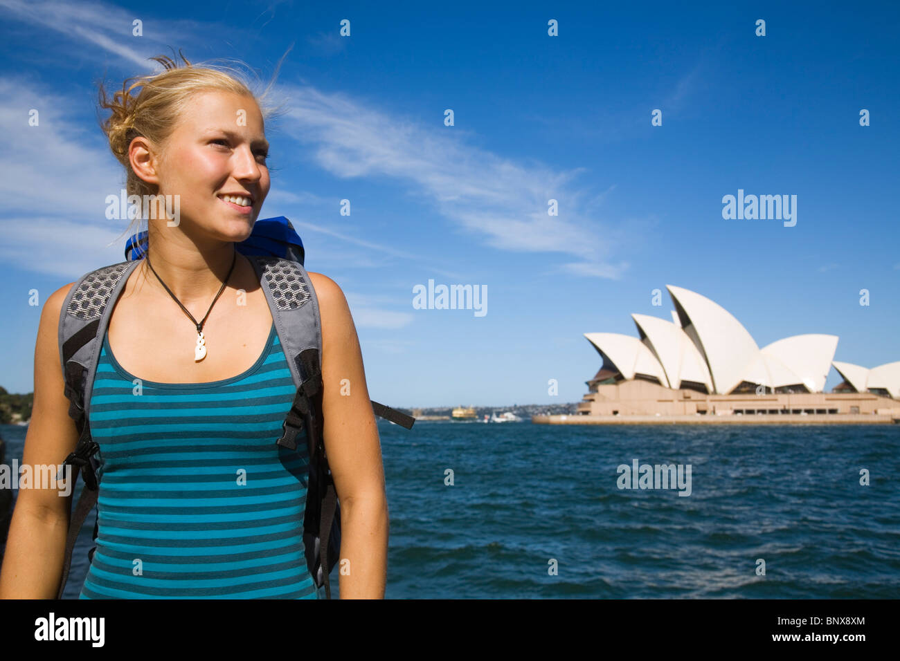 A backpacker with the Opera House in the background.  Sydney, New South Wales, AUSTRALIA. - Stock Image